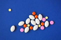 Medicine pills on blue background. Stock Photo