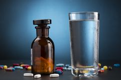 Pills medicine bottle and glass of drink water Stock Photo