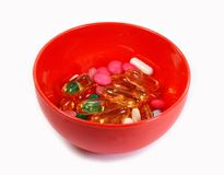 Medicine pills in in a bowl isolated on white. Royalty Free Stock Photography