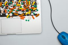 Medicine pills and capsules type and color on computer keyboard. Medicine drug pills and capsules of different type and color on computer keyboard and mouse royalty free stock photos