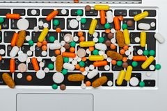Medicine pills and capsules type and color on computer keyboard. Medicine drug pills and capsules of different type and color on computer keyboard closeup, on royalty free stock images