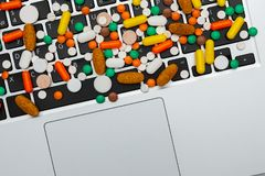 Medicine pills and capsules type and color on computer keyboard. Medicine drug pills and capsules of different type and color on computer keyboard closeup, on royalty free stock photo
