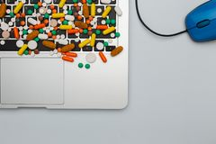 Medicine pills and capsules type and color on computer keyboard. Medicine drug pills and capsules of different type and color on computer keyboard and mouse royalty free stock photography