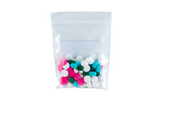 Medicine pills. Group of medicine pills with pink, white and green/blue color in bag on white background stock images