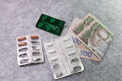 Medicine, pills, money, on a gray background, Ukrainian hryvnia. Medicine, pills, money, on a gray background Ukrainian hryvnia Royalty Free Stock Photo