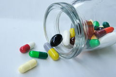 Medicine pills spilling out. From a glass bottle Royalty Free Stock Image