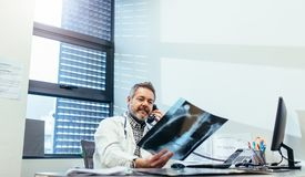 Doctor examining x-ray and talking on phone Royalty Free Stock Photo