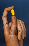 Medicine. A robot like wooden hand, with a pill between two fingers Stock Image