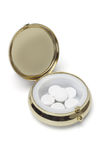 Medicine in round metal pill container Royalty Free Stock Image