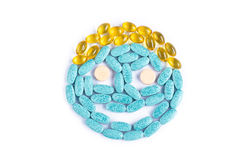 Medicine smiley face. Smiley face made from blue pills, gold capsules and have orange tablets for eyes on white background Royalty Free Stock Photos