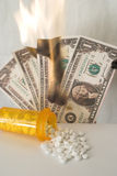 Medicine spilling from bottle with money burning in background. Medicine bottle on table with white tablets spilling out and four US dollar bills burning in royalty free stock images