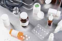 Medicine and Stethoscope on Stainless Steel Surface. Medicine bottles pills and stethoscope on a stainless steel surface. Horizontal format Stock Images