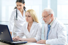 Medicine team. Three medicine workers looking at monitor Stock Photography