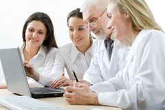 Medicine team. Four medicine workers looking at monitor Stock Photos