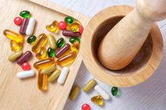 Medicine and vitamin on wooden plate Royalty Free Stock Photo