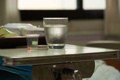 Medicine and water for patient admitted in hospital. A capsule of medication and a glass of cold water for patient admitted in hospital. Meal in plates for stock photo