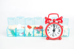 Medicine in weekly pill box and red alarm clock Royalty Free Stock Photo