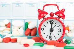 Medicine in weekly pill box and red alarm clock Royalty Free Stock Image