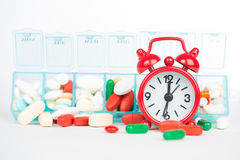 Medicine in weekly pill box and red alarm clock Royalty Free Stock Photography
