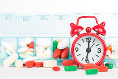 Medicine in weekly pill box and red alarm clock Stock Photography