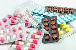 Mediciner och injektionsspruta på vit bakgrund Royaltyfri Foto