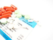 Mediciner på sjukförsäkringkortet som visas gruppfördelar som isoleras på vit bakgrund Royaltyfri Foto