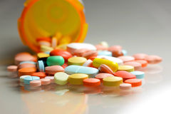 Medicines. Many colorful pills spilled from orange bottle Royalty Free Stock Photography
