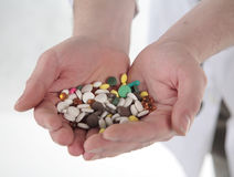 Medicines. Considerable quantity of medicines in hands of the person in a white dressing gown Royalty Free Stock Image