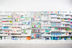 Medicines Arranged In Shelves At Pharmacy. Defocused image of medicines arranged in shelves at pharmacy royalty free stock photos
