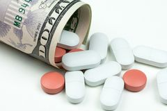 Medicines, capsules and pills on dollar bills Royalty Free Stock Photography