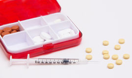 Medicines in the form of pills and injections. Pill box with pills and syringe Stock Images