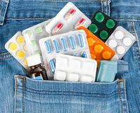 Medicines in jeans pocket. Many different colorful medicines in jeans pocket royalty free stock photography