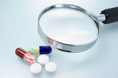 Medicines and magnifier. Stock Photos