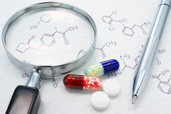 Medicines, magnifier and structure formula. Royalty Free Stock Image