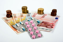 Medicines and money. Medicines on paper money and euro coins Royalty Free Stock Image