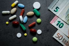 Medicines and money. Expensive medicine. Heart. Medicines on a black background Stock Photos