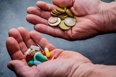 Medicines and money in human hands. Medicines and money. Expensive medicine. Heart. Medicines on a black background Stock Image
