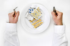 Medicines and pills for dinner. Man holding fork and knife ready to eat Stock Photo