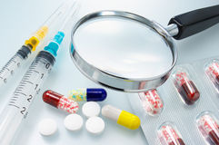 Medicines, syringes and magnifier. Stock Photo