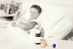 Medicines on table with boy in bed Stock Photos