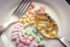 Medicines, vitamins, spoon and fork on a white plate. Royalty Free Stock Images