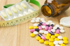 Medicines and waist circumference in closeup. View with some space on table wood backgrounds royalty free stock photo