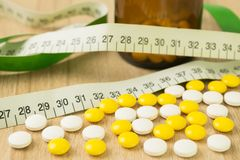 Medicines and waist circumference in closeup on table wood. Backgrounds stock image