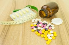 Medicines and waist circumference on table wood. Background stock photo