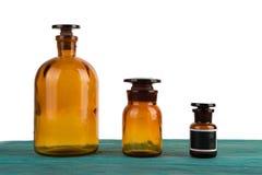 medicinflaskor på den isolerade trätabellen arkivfoton