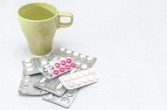Medicinminnestavlapreventivpillerar nära en kopp av vatten Top beskådar isolerat Fotografering för Bildbyråer