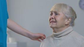 Medicinsk arbetare som tröstar den desperat skriande äldre kvinnan i vårdhem lager videofilmer