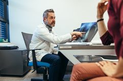 Medicinsk doktor som förklarar röntgenstråleresultat till patienten arkivfoto