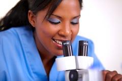 Medicinsk doktorskvinna som använder ett mikroskop Arkivbild