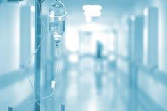 Medicinsk droppande på bakgrunden av sjukhuskorridoren Royaltyfri Foto